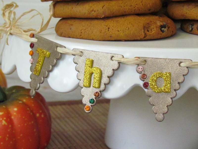 Thanksgiving Table Mini Banner. Create a mini table banner for your Thanksgiving dessert table using chipboard banner, paint and mini buttons