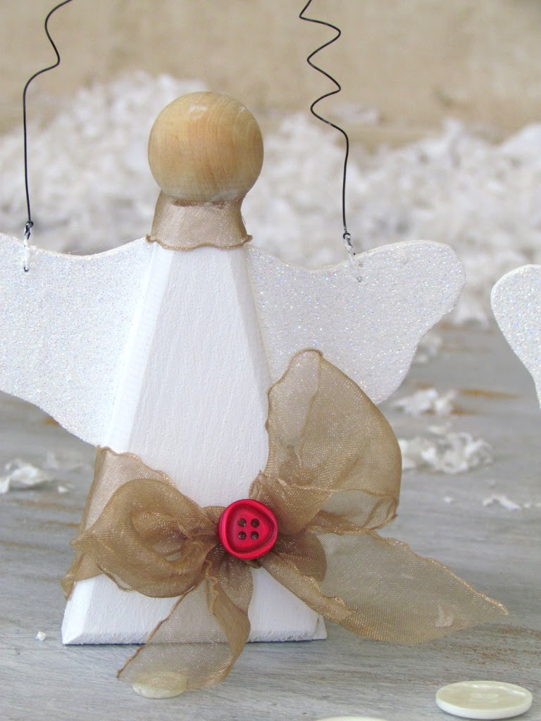 Snow Angel Ornaments made out of wood angels painted white and made sparkly with glitter, buttons and ribbon