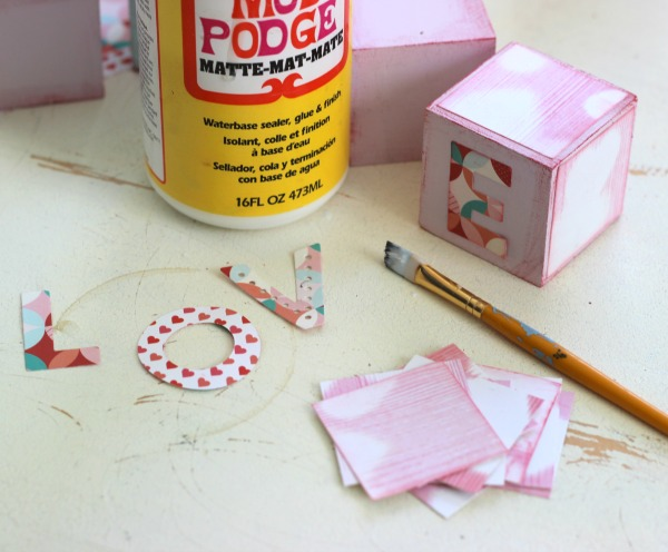 Use Mod Podge to adhere paper on to wood blocks .