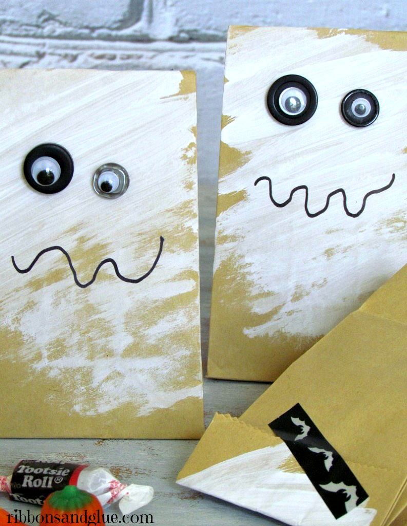 Easy Button Eye Halloween Treat Bags. All you need is small kraft bags, paint, buttons and googly eyes! Kids can even make these for their friends.!