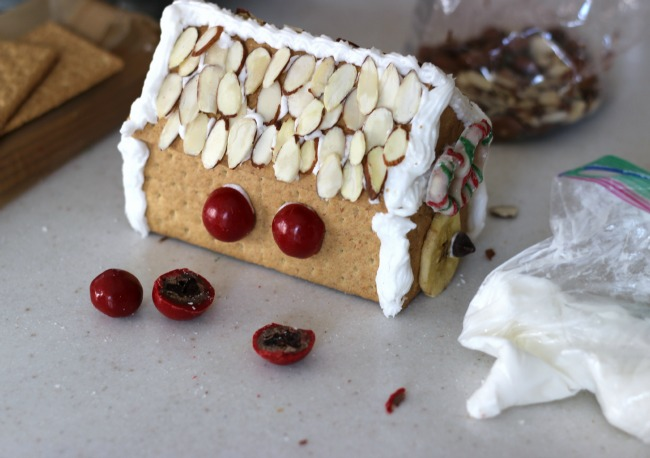 Decorating graham cracker house with better food options instead of candy like almonds.