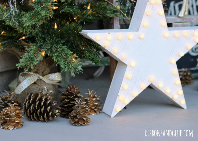 Gold Pine Cone and a Marque Star decorates a Rustic Christmas front porch