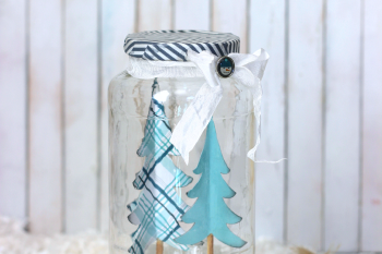 DIY Winter Snow Jar made from an upcycled sauce jar, paper trees and fake snow. Creative way to bring winter in to your homw without the mittens.