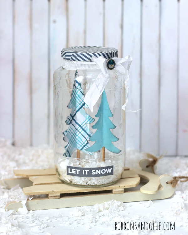DIY Winter Snow Jar made from an upcycled sauce jar, paper trees and fake snow. Creative way to bring winter in to your home without the mittens.