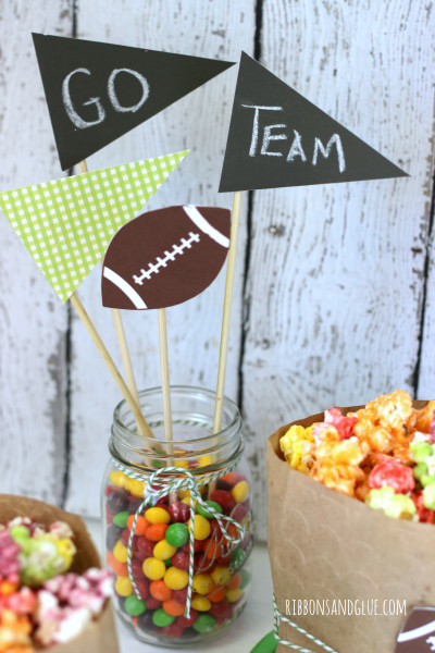 Quick and Easy Superbowl Centerpiece Idea. Cut flag out of chalkboard paper and adhere on to sticks then display flags in a Mason Jar of Skittles. Could also use team color candies!