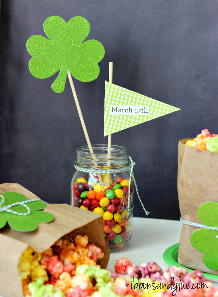 Easy St. Patrick;s Day centerpiece idea. Simple pennant flags stuck in a mason jar of Skittles!