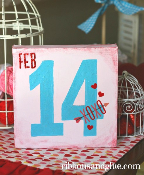 DIY Painted Valentine's Canvas . Paint an 8x8 canvas with the number 14 using chalky finish paints and embellish with scrapbooking stickers. Easy Valentine's Day decor!