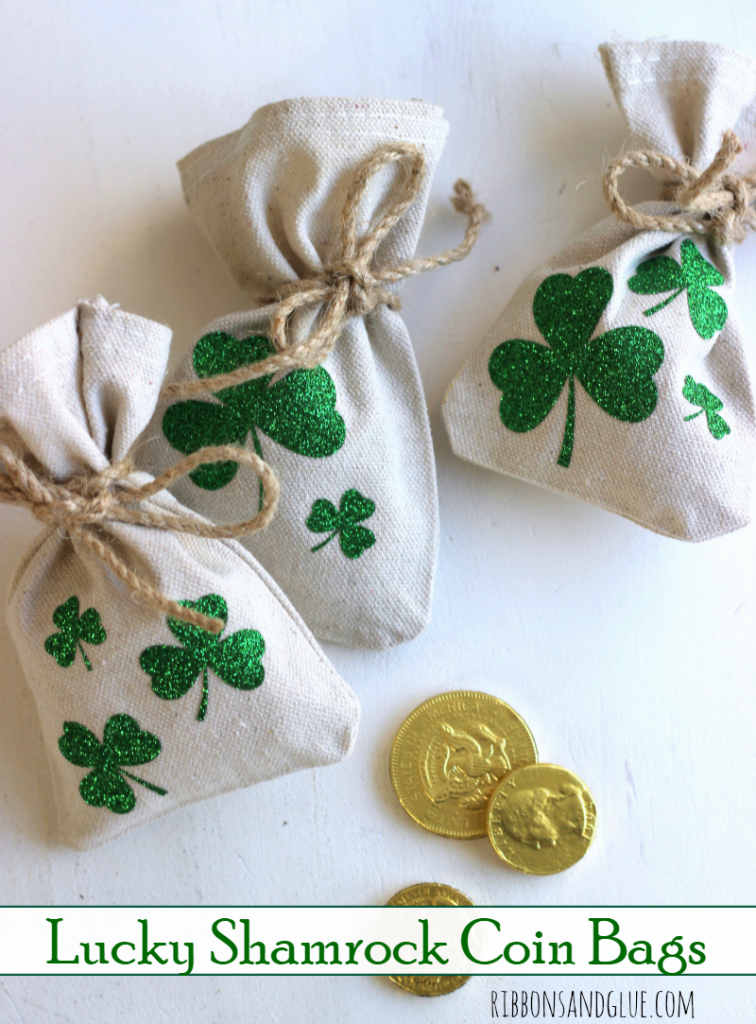 DIY Lucky Shamrock Coin Bags made out of drop cloths and green glitter heat transfer vinyl. Perfect St. Patrick's Day treat filled up with gold chocolate coins.
