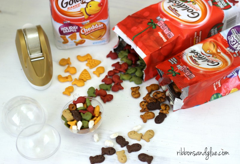. Fill up plastic ornaments with Goldfish crackers and attach tag. Easy Christmas Kids Craft Idea.