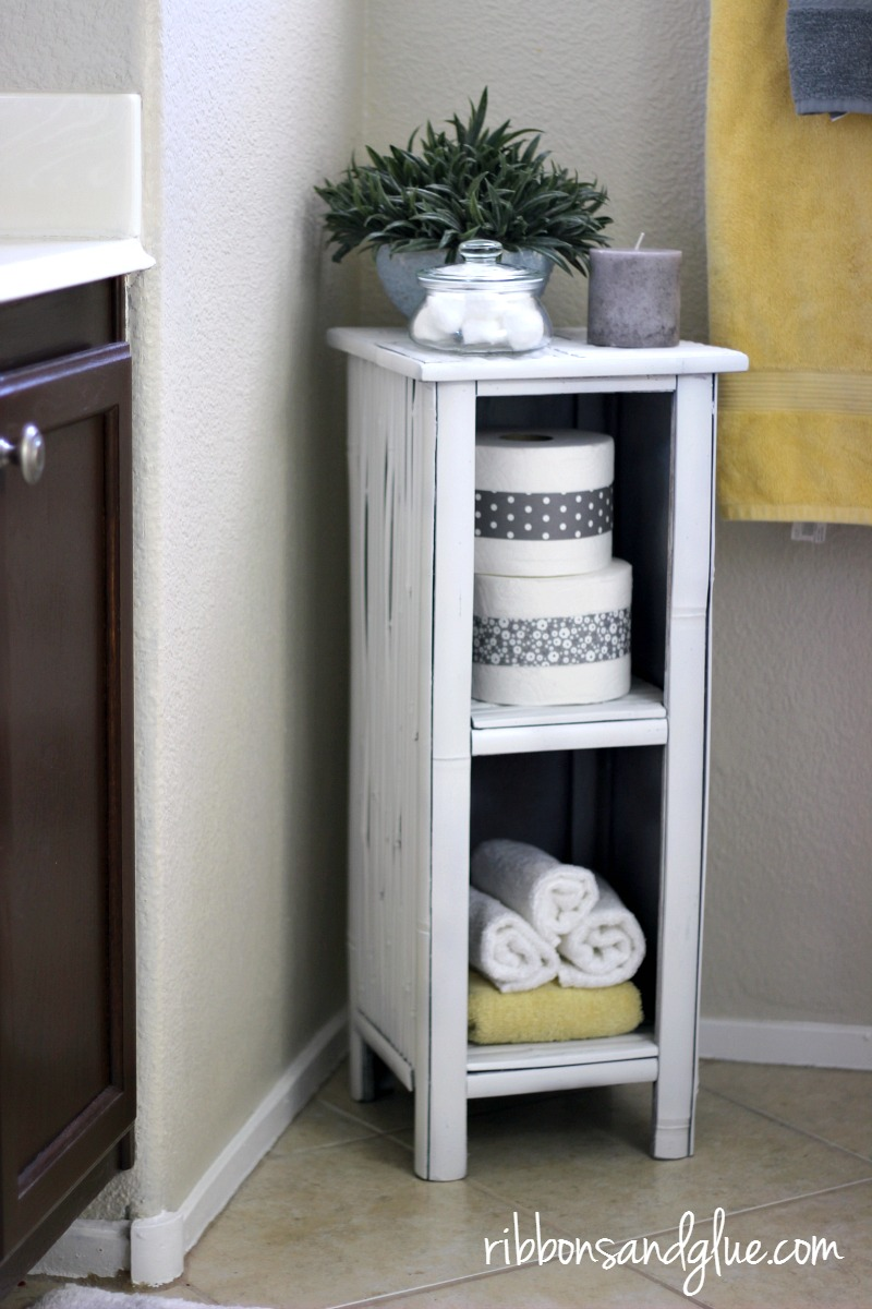 A side table found in the trash creates a simple guest bathroom refresher with freah linens and fancy toilet paper.