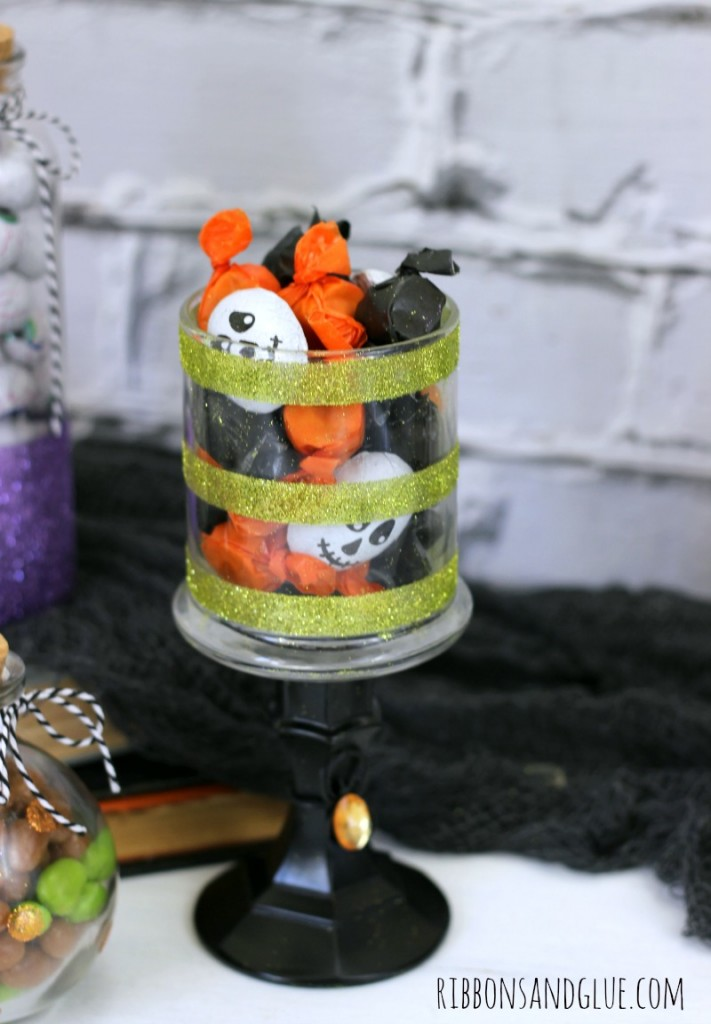 Create DIY Halloween Candy Glitter Jars out of empty glass jars, glitter and adhesive. Spooky cute to fill up with candy for Halloween.
