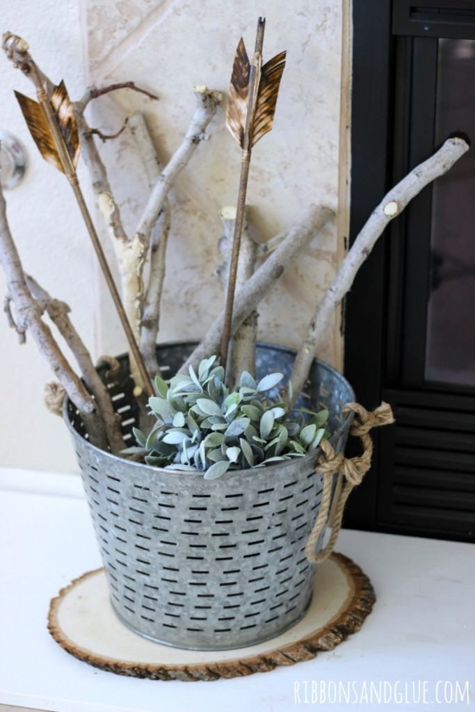 Olive Bucket with branches on fireplace hearth