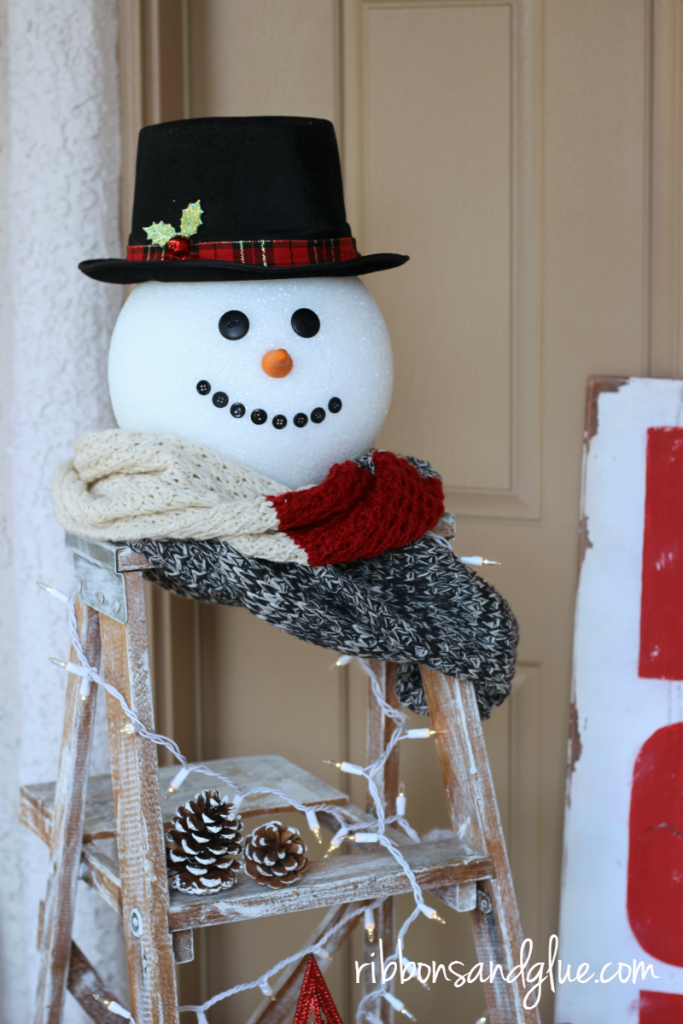Christmas Snowman Ladder. Large foam ball turned in to a snowman head displayed on top of a vintage ladder.