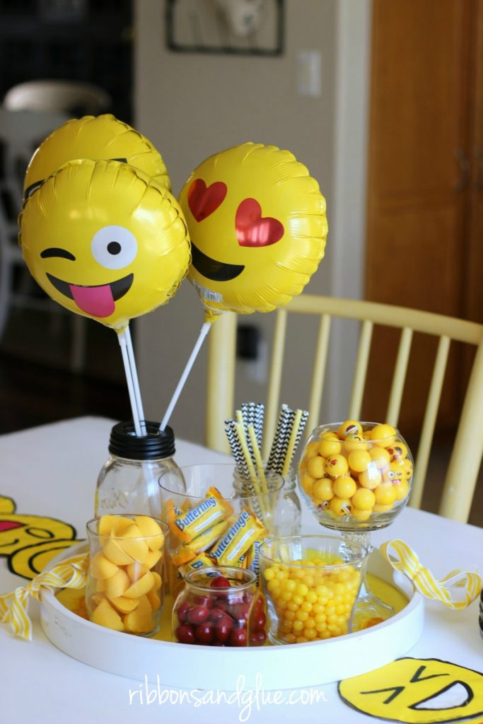 Emoji Birthday Party Table complete with emoji party decorations, yellow candy, DIY table runner and Poop