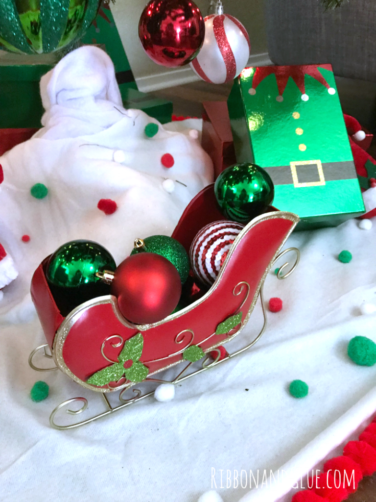 Christmas bulb ornaments in a sleigh under the tree